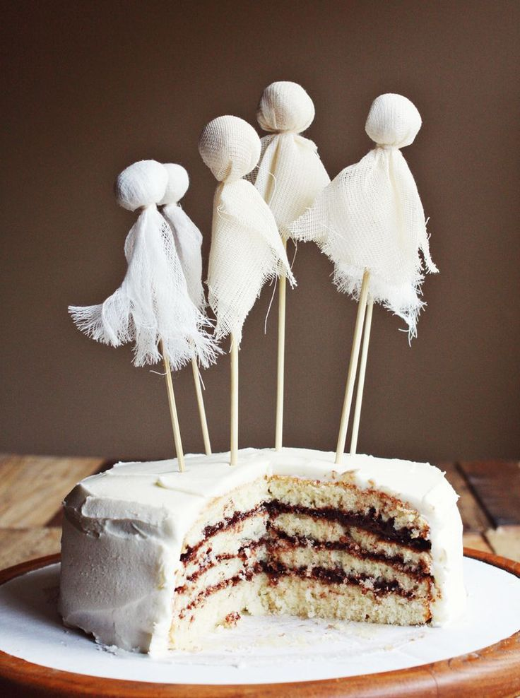 Create mini-ghost cake toppers from wooden skewers, cotton balls, cheese cloth & thread. Simply cut small squares of fabric to cover the cotton ball and tie onto the top of the skewer for a rather impressive Halloween cake decoration.