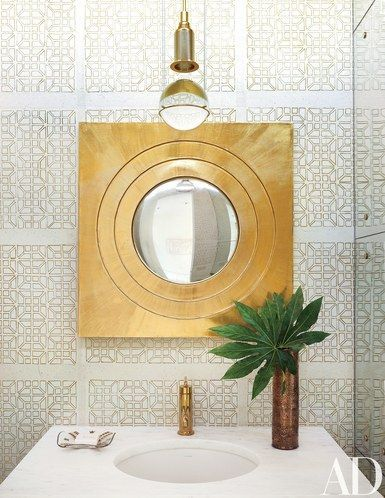 A Cannon/Bullock wallpaper brightens the powder room; the Günther Leuchtmann pendant light is from Plug, the mirror is vintage Mexican, and the faucet is by Kohler | archdigest.com