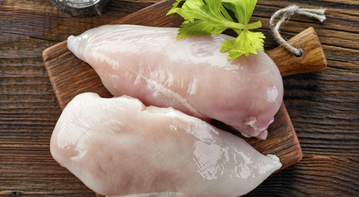 raw chicken fillets on wooden cutting board, top view