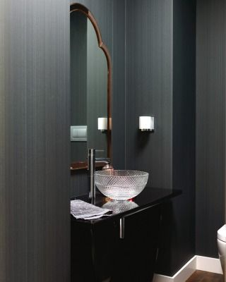 A cut-glass bowl basin and vintage Italian gold mirror lend the bathroom glamour and surprise.