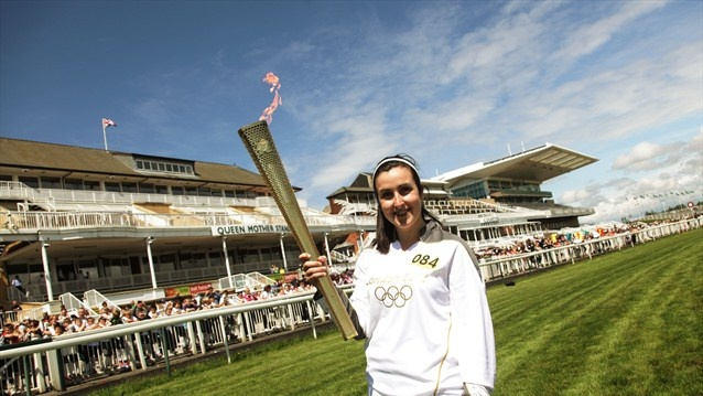 The Flame at Aintree Racecourse  Torchbearer Kimberley Cooper holds the Olympic Flame on the race track at Aintree, during Day 14 of the London 2012 Olympic Torch Relay.