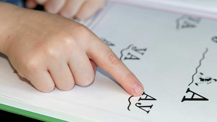 Different types of dyslexia.  Close up of a child pointing out letters as they read