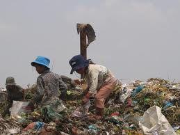 Graag wil ik je meenemen om een kijkje te nemen bij de grootste afvalberg in Cambodja, de afvalberg van Phnom Penh, de hoofdstad van Cambodja. Vele duizenden baby´s, kinderen en ouderen leven van wat de vuilnisbelt oplevert. Gezinnen kunnen hier een dagelijks inkomen bijeen scharrelen van gemiddeld € 0,50, ongeveer 2000 Cambodjaanse Riels. Rond de vuilnisbelt staan zo om en nabij de zevenduizend zeer schamele hutjes waarin deze mensen leven, het gaat om naar schatting twintigduizend mensen.
