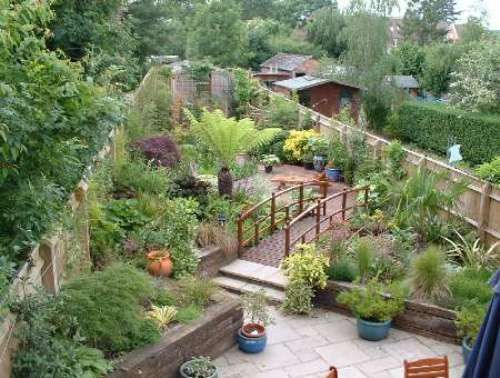 making the most of an awkward shaped yard. check out that garden bridge too