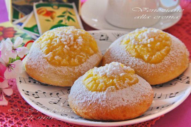 """Οι """"βενετσιάνες"""" είναι πεντανόστιμα αφράτα μπριοσάκια με επικάλυψη κρέμας ζαχαροπλαστικής, πασπαλισμένα με ζάχαρη και γρανέλλα ζάχαρης. Καθαρά ιταλικό παρασκεύασμα, με καταγωγή απο τη βόρεια Ιταλία, διαδεδομένο όμως αρκετά και στο ιταλόφωνο καντούνι του Τιτσίνο στην Ελβετία."""