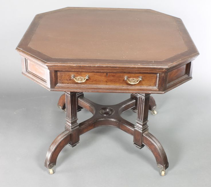 """Lot 936, A Maples & Co octagonal mahogany aesthetic movement library table with inset writing surface fitted 2 drawers, raised on 4 turned and fluted columns with X framed stretcher 29""""h x 36""""w x 36""""d est £200-250"""