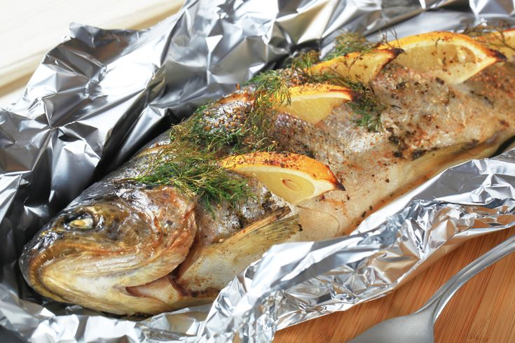 Pstrąg pieczony jest idealnym daniem na postny piątek (lub dowolny inny dzień). Łatwość przygotowania potraw z pstrąga w pełni tłumaczy popularność tej ryby. Proponujemy przepis na pstrąga pieczonego w piekarniku, podawanego z sałatą lodową z pomidorami i sosem winegret. (fot. depositphotos)