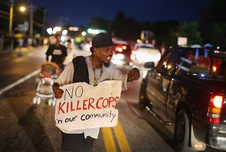 A demonstrator holds up a sign along West Florissant Avenue in Ferguson, Missouri, after teenager Michael Brown was gunned down by police on 9 August.