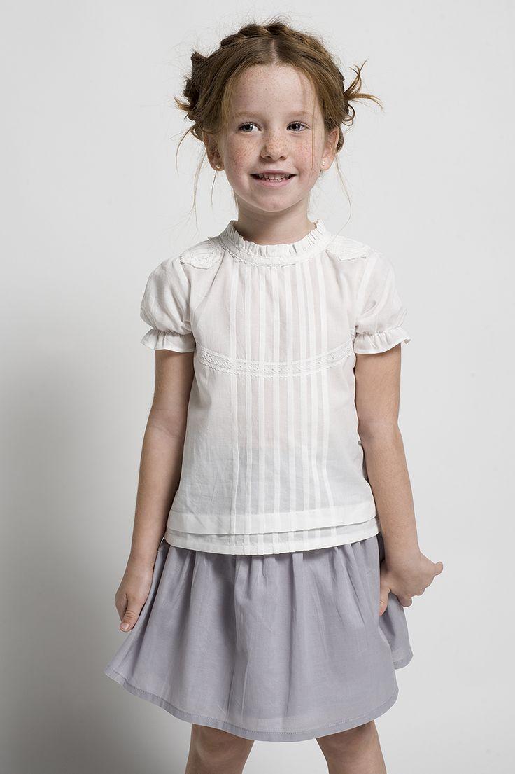 Conjunto de niña formado por una falda gris y una blusa de jaretas.