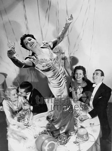 Frau tanzt auf dem Tisch bei einer Silvesterfeier Timeline Classics/Timeline Images #Feiern #Silvester #Neujahrsfeier #Neujahrstag #31.Dezember #Jahresende #Party #Brauchtum #historisch #schwarzweiß #historical #Nostalgie #nostalgisch #Partyoutfit  #vintage #Damenmode #Partykleid #Luftschlangen #tanzen #Frau #1930er #1930ies