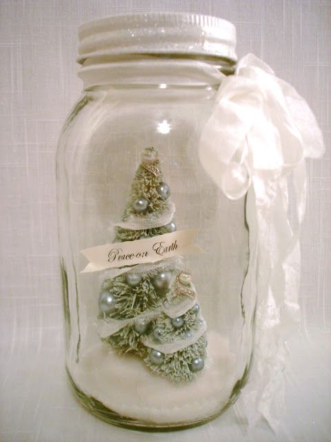 Green bottle brush tree in a mason jar decoration, pearls, peace on earth banner, glitter lid, artificial snow.