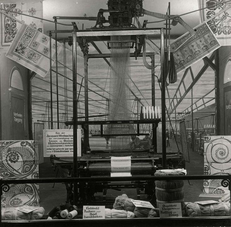 Weverijen. Machinaal weven. Een Jacquard weefmachine in de etalage van V&D, Amsterdam, 1915. De machine wordt door V&D gebruikt om monogrammen e.d. in linnen en damast te weven.[Joseph Marie Jacquard (1752-1834) realiseerde de eerste volautomatische weefmachine, waardoor met behulp van een soort ponskaarten ingewikkelde patronen geweven konden worden.]