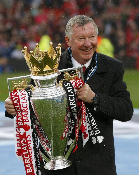 Manchester United manager Alex Ferguson poses with the English Premier League trophy at Old Trafford stadium in Manchester