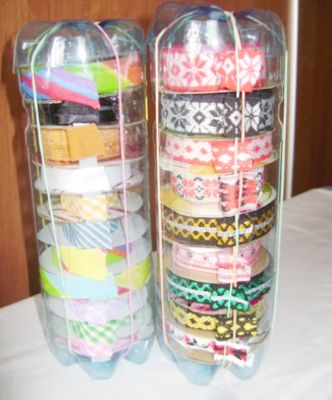 Make a simple ribbon dispenser using soda bottles. Cut the top off of two bottles, squish the two bottom halves together and cut a slit in the side. Use rubber bands to hold the bottles together and to keep the ribbon ends in place.