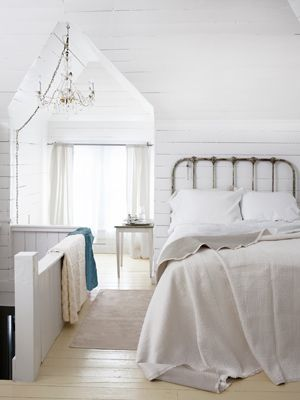 Subtract color to emphasize architecture. This homeowner whitewashed the walls in her attic to heighten the drama of its pointed arch. #decoratingideas #bedroomdecor