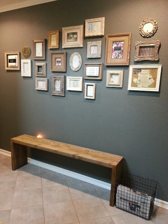Busy wall: shabby chic photo frames, reclaimed bench, vintage news paper basket, disguised light switch and A/C panel