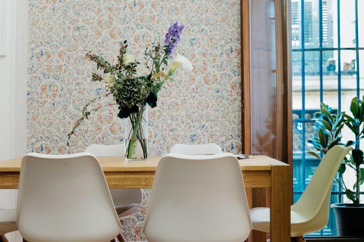 Destaca el papel pintado que hace descatar la sillas y la mesa de estilo nórdico.