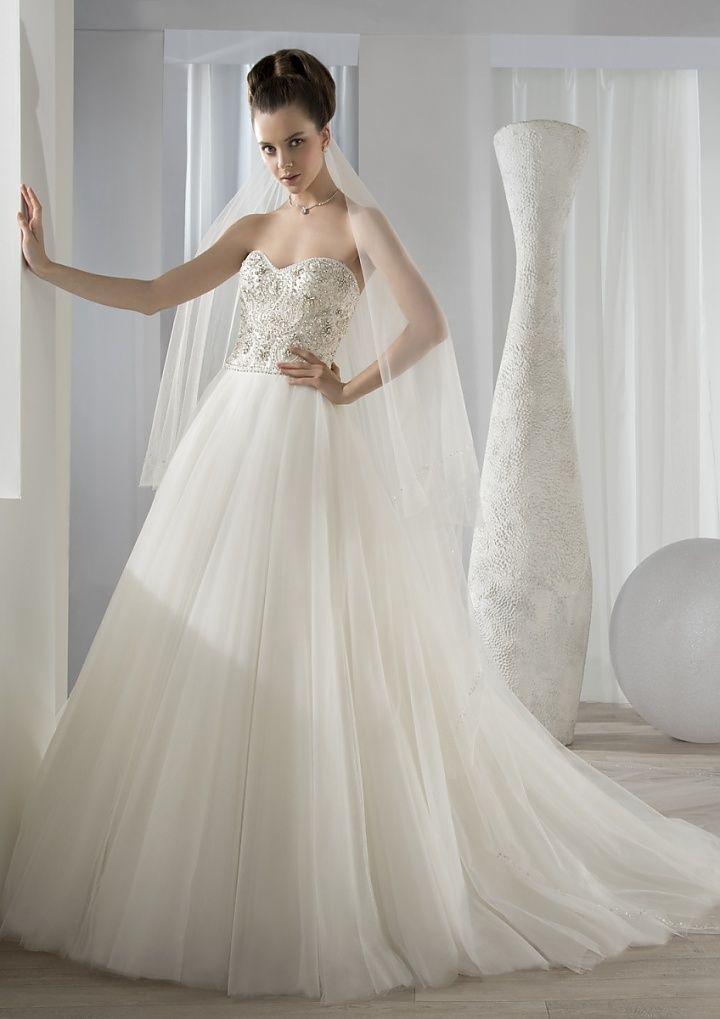Deze prachtige A-lijn trouwjurk is in één woord schitterend; het strapless lijfje heeft een sweetheart halslijn. De stenen en kralen geven een extra rijk cachet aan de jurk. De wijde tule rok van tule en de sluier maakt dat de bruid zich als een prinses voelt in deze jurk. #alijn #strapless #tule #prinses #koonings