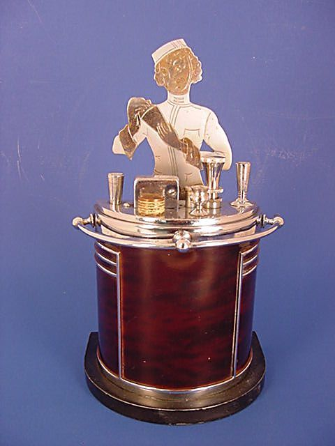 """This is a large 7 1/2"""" tall Ronson Touch Tip art deco lighter in the shape of a bar with the figure of a female bartender behind it. ca 1936 this lighter is specially made for Ronson by the Artmetal Works Inc., of Newark NJ"""