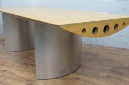 A totally unique piece! If you are looking for a substantial table for your boardroom or home, this is the one for you! Designed and made with aircraft styling. The top has a flat surface but is shaped like a wing from lpywood and the bases are clad in aluminium with riveted seams.