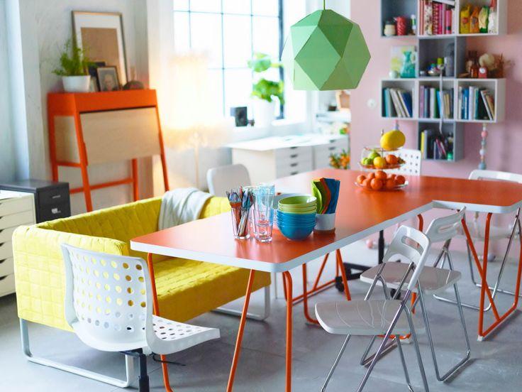Una zona pranzo con due tavoli arancioni e sedie bianche sotto a un lampadario verde - IKEA