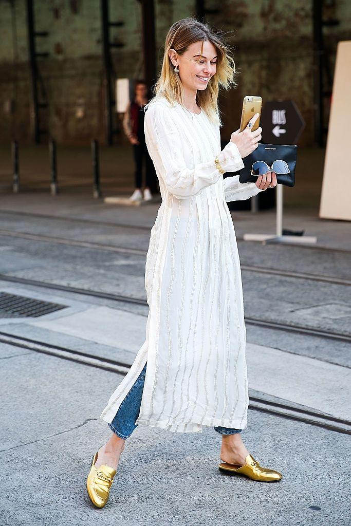 Natalie Cantell    ニュージーランド出身のモデルで、ときにはスタイリストやゲストエディターとしても活動しているナタリー。さらりとした風合いの白いドレスとデニムパンツをレイヤードしたスタイリングに、ブレスレットとスリッポンシューズでゴールドを効かせた。手にしたiPhoneも金色で、カラーコーディネートはバッチリ!   写真2:この日はポップなカラーリングのボーダーニットを...