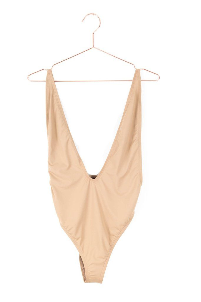 Low V-neck one piece swimsuit in beige. High leg cut with cheeky bottoms and an open back. Gold accents on adjustable straps. Made and manufactured in the USA a