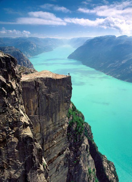 Standing at the edge of the world, on the Pulpit Rock, Preikestolen, in Forsand, Ryfylke, Norway