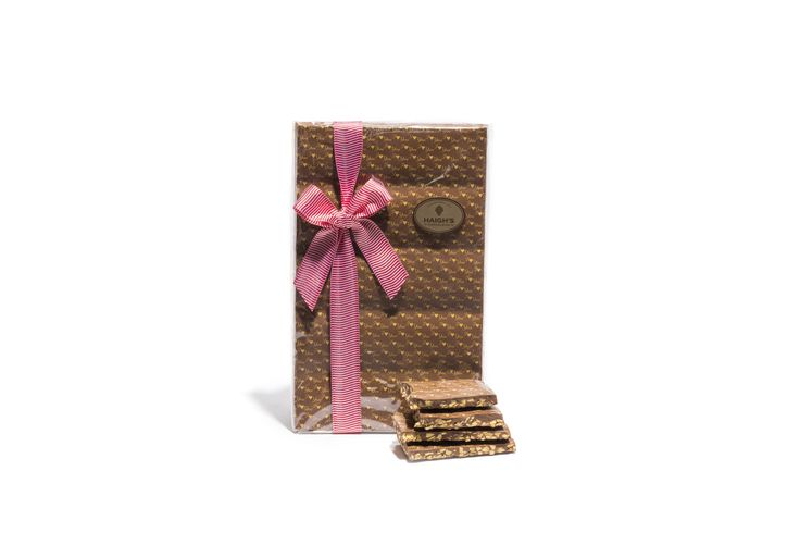 """Say """"I love you"""" with a Haigh's Valentine's Milk Honeycomb Block. Premium milk chocolate blended with crunchy honeycomb pieces and heart decorated.  Ready to give to your Valentine in a ribboned gift bag."""