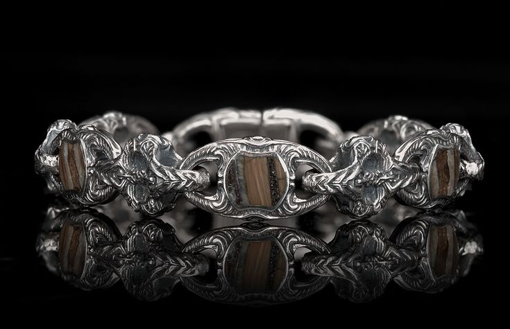 The Squire highlights our rare fossil wooly mammoth tooth inlaid into long and bold sculpted sterling silver links. The mammoth tooth dates back at least 10,000 years, and is found on the seafloor in select areas around the world. Processing (after discovery) takes almost three years. The results are stunning – each inlay, and each bracelet, is absolutely unique by the very nature of the material. Finished with a precision machined stainless button lock inlaid with a genuine citrine…