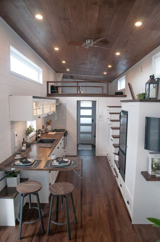 Die Küche verfügt über eine Holztheke, beleuchtete Schränke, einen 12-Volt-Kühlschrank, zwei