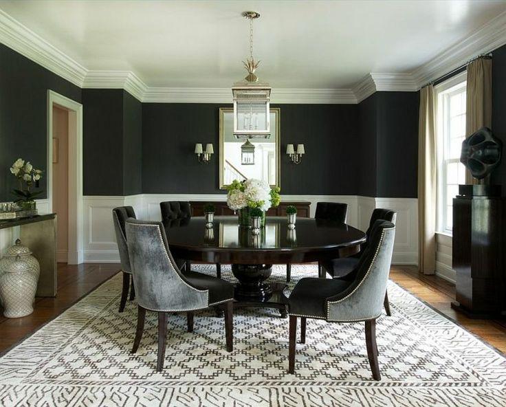 demi mur noir, une table ronde en bois sombre et un tapis en noir et blanc dans la salle à mnger