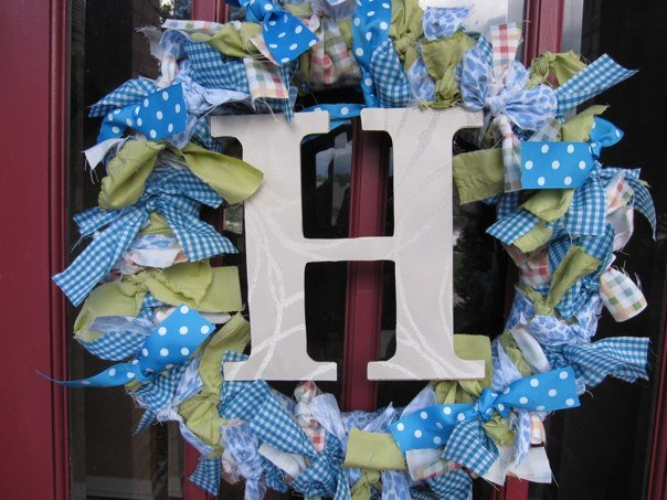 "How to make the wreath for Brooke's room - 4 types of cloth (1/2 yard ea. cut into 2""x18"" strips), ribbon (2"" wide),  straw wreath (18"") shown in this picture), something to hang from the middle, and a hook"