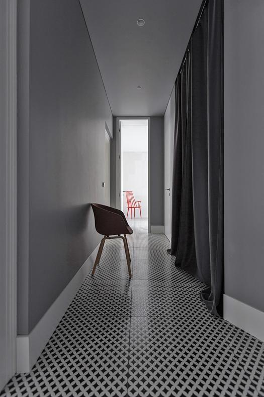 REINVENTARE IL CLASSICO A STRASBURGO: PASSAGIO IN GRIGIO Il lungo corridoio che conduce al bagno è rivestito in ceramiche optical black&white. Una tenda in pesante velluto grigio, tono su tono con le pareti, nasconde una piccola cabina armadio.