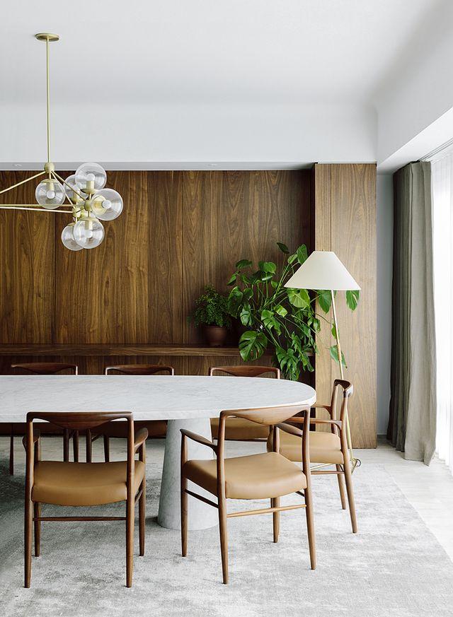 Dans la salle à manger, la grande table ovale en marbre d'Angelo Mangiarotti, sous une suspension Roll & Hill, permet de fluidifier le passage vers le living,pendant qu'un tapis en soie adoucit l'atmosphère. Lampadaire Hase (Kalmar).