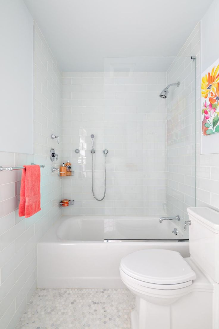Pops of pink and yellow add a fun, feminine touch to this all-white bathroom.