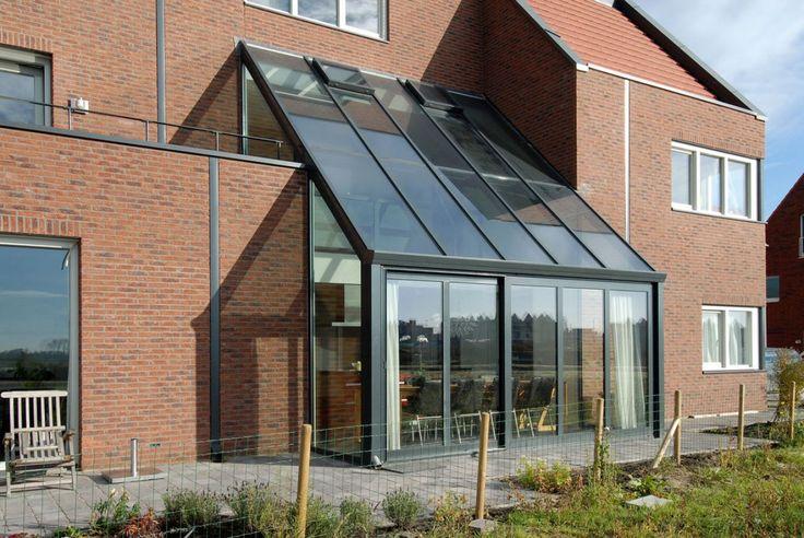 Deze Reynaers serre of tuinkamer maakt van je huis een lichte en bijzondere plek! Het grijze aluminium voegt een verrassend element toe aan de moderne nieuwbouwwoning.