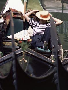Gondolier Relaxing in Gondola, Venice, Italy