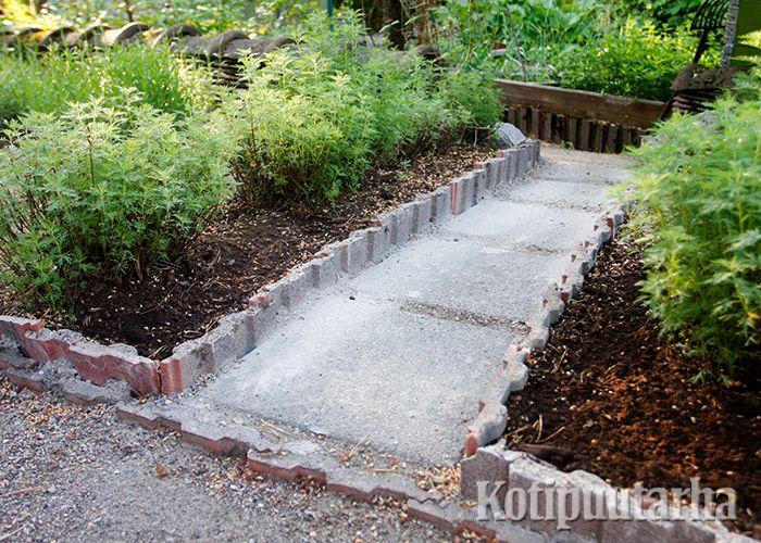 Kierrätysmateriaalien käyttö on suosittua puutarharakentamisessa. Tässä keittiöpuutarhan rajaukset on toteutettu vanhoilla kattotiilillä.