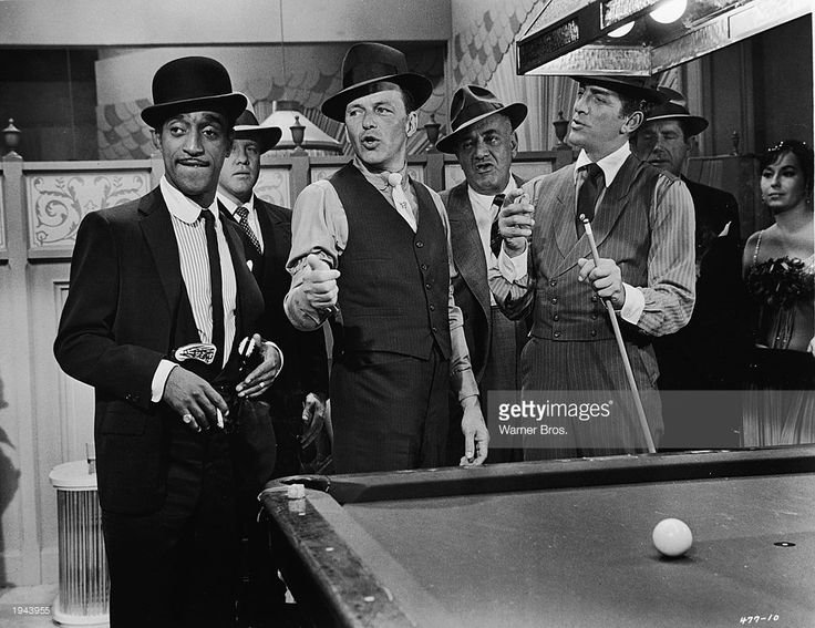 American singers and actors Sammy Davis Jr. (1925 - 1990) ( left), Frank Sintra (1915 - 1998), Dean Martin (1917 - 1995), and others in a still from the film, 'Robin and the Seven Hoods,' directed by Gordon Douglas, 1964.
