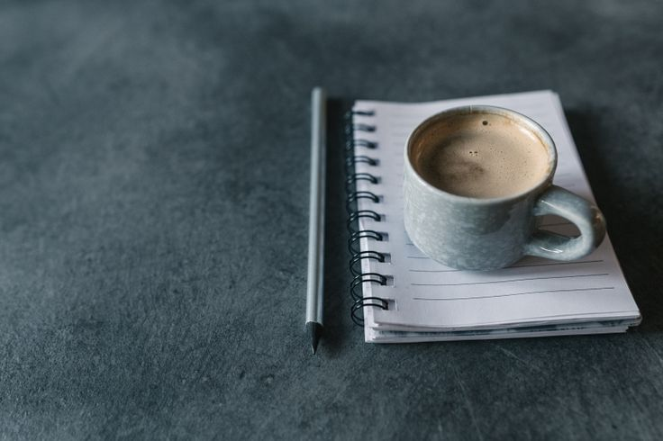 Cup of coffee on a empty notepad and copy space