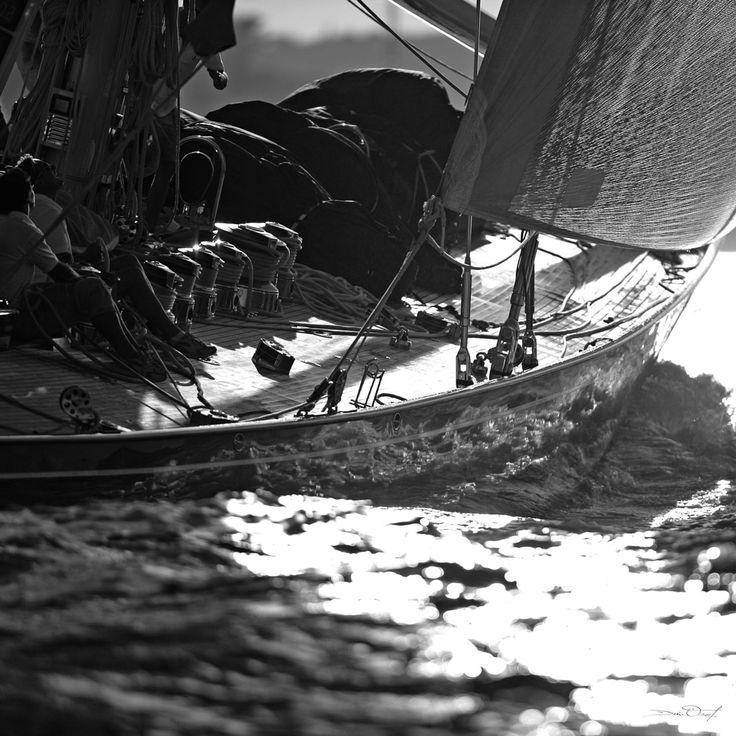 Photographie 30x30 cm, en noir et blanc. Photographie prise sur la côte  bretonne. Le bateau à voile file sur la mer face à un soleil couchant.