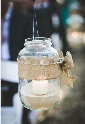 This is cute and simple...hanging jar tied in burlap ribbon bow, with sand and candle.