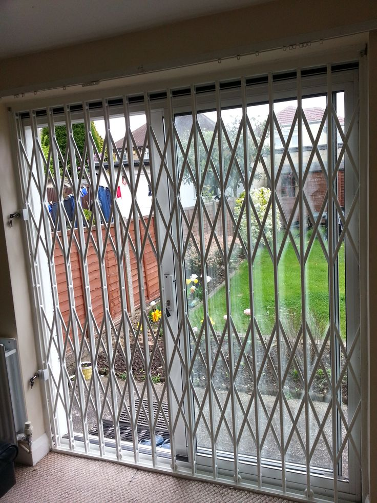 RSG1000 Retractable Security Door Grilles fitted internally to the main entrance of the living room of a residential complex in Fulham
