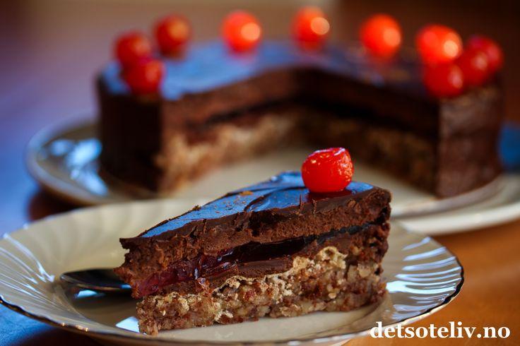 Sponset innlegg. Hei! I dag vil jeg gi dere oppskrift på en virkelig herlig konfektkake til jul! Troikakake består av lag på lag med mandelbunn, nougat, bringebærgelé, luftig sjokoladekrem og sjokoladeglasur. For å få julefarger, har jeg pyntet med gullglitter og cocktailbær. Kaken smaker nydelig og holder seg god i mange dager. En kake som garantert vil bli populær blant gjestene dine!