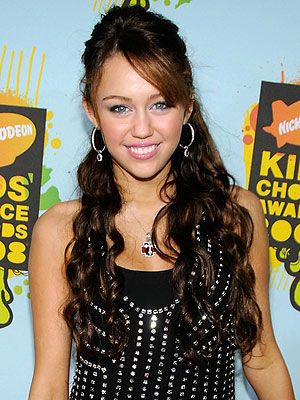 Miley with wavy, glossy hair in an updo and a side swept fringe. #mileycyrus #hair