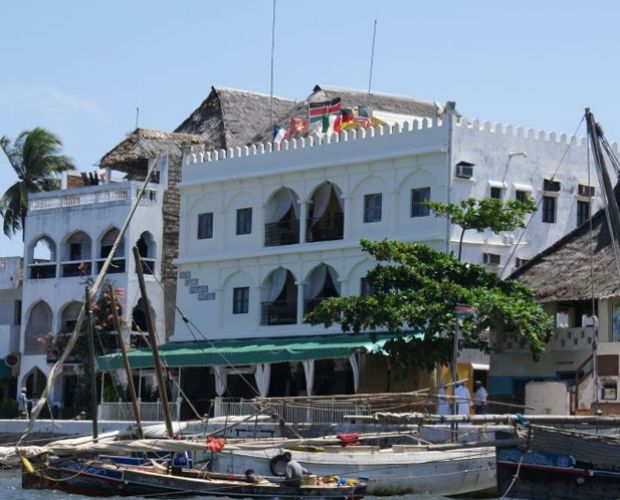 The New Lamu Palace Hotel -is located along the shorefront of the old stone-town on the island of Lamu,  New Lamu Palace Hotel in Lamu offers accommodation in 22 smart comfortable rooms and 3 suites in its outstanding Arabic-style facade. All the rooms are comfortable, air-conditioned and have en-suite bathrooms with hot & cold running water supply. 1st and 2nd floor rooms have beautifully furnished lounge areas; presenting panoramic views of the ocean and gardens.