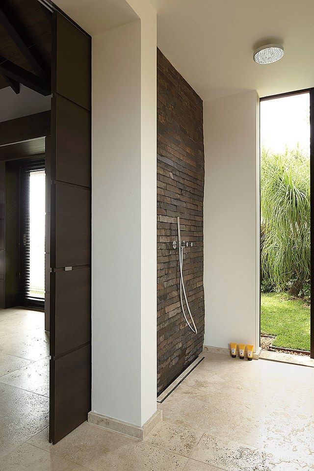 The floor is travertine and the shower, which opens to a garden, includes a wall of Balinese slate tile in Wolfgang Ludes's airy master bath, in a St. Barts residence he designed with architect Johannes Zingerle.