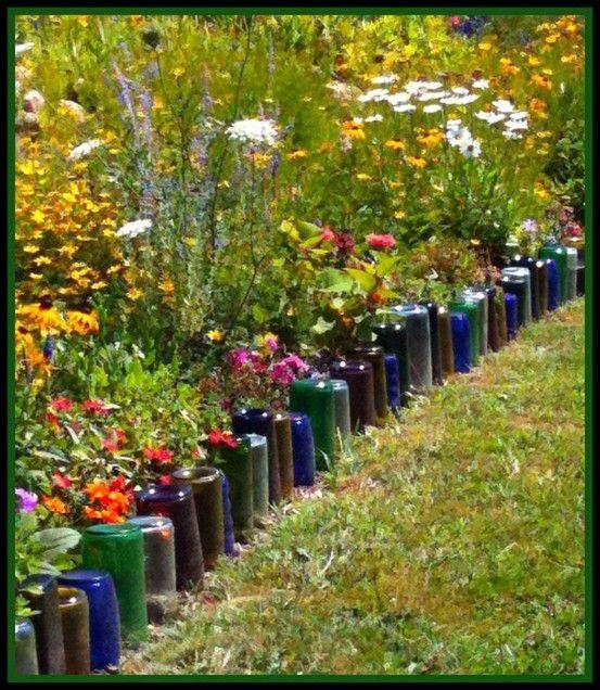 Colored glass bottles turned upside down for garden border.