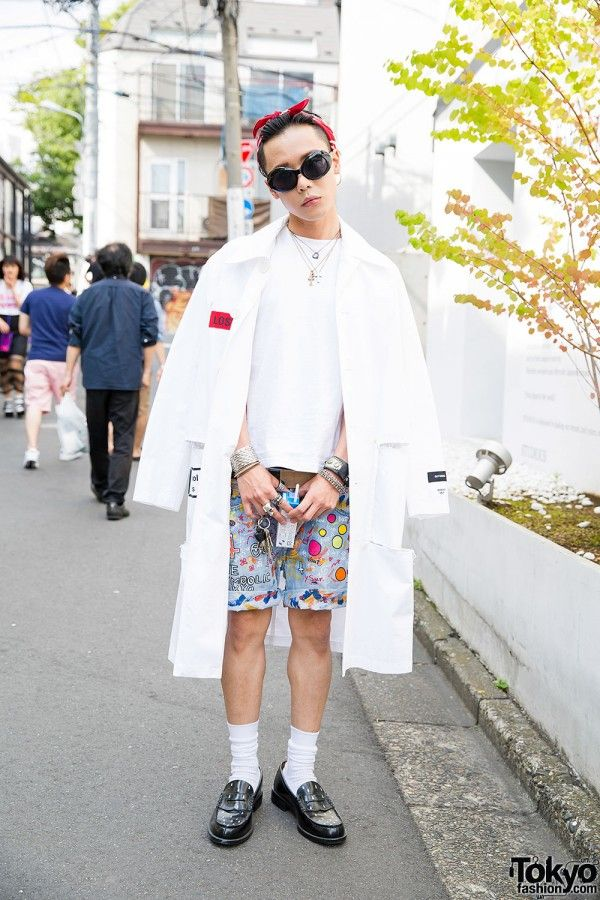 """S_youBG is the creative director for The Symbolic Tokyo. He's wearing a Hyein Seo coat – embroidered with """"Antwerp"""" and a pair of red skulls on the back – over a white t-shirt and hand-decorated denim shorts, both from The Symbolic Tokyo. His black penny loafers painted with white droplets are worn over white socks. Accessories: red bandana, dark sunglasses, and various jewelry – including a skull ring, various bracelets, hoop earrings, and necklaces. He likes the fashion of Yves Saint…"""